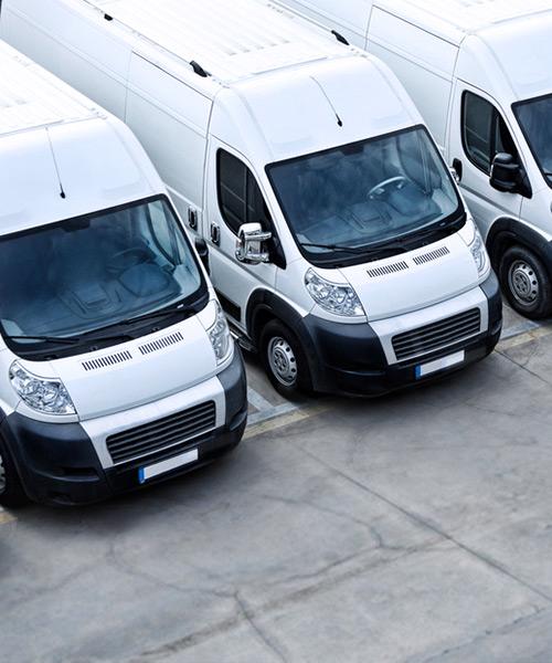 Mehrere Transporter in einer Reihe auf einer Betonfläche